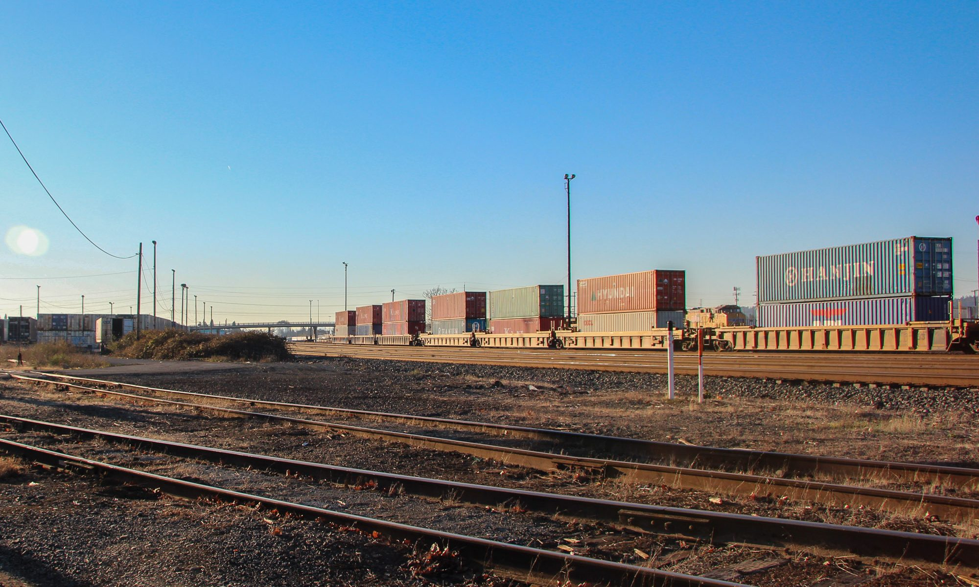 This article is about Docker containes, but here are some shipping containers on railcars. Portland, OR, 2011.